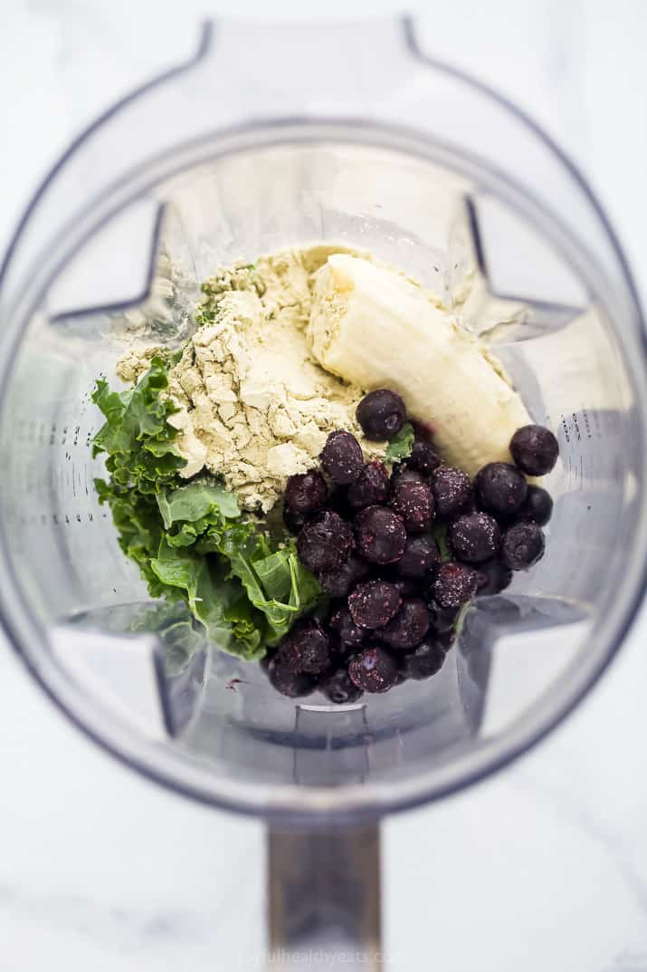 A Blender Filled with Fruit, Kale and Protein Powder