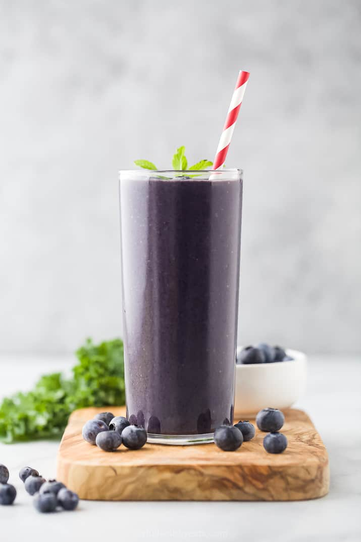 A Kale Protein Smoothie in a Tall Glass with a Red and White Striped Straw