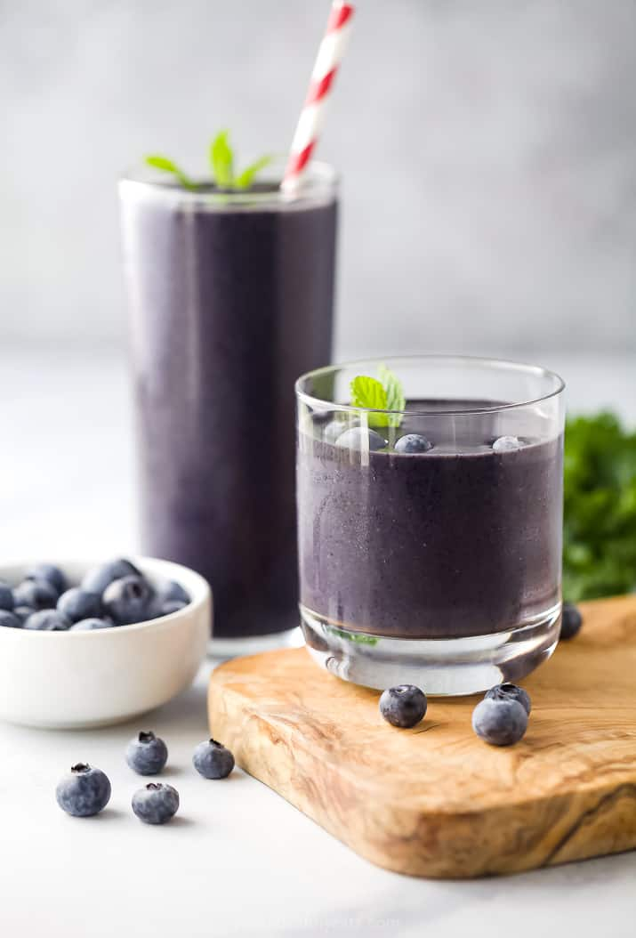 Two Glasses of Kale Smoothies Next to a Bowl of Fresh Blueberries