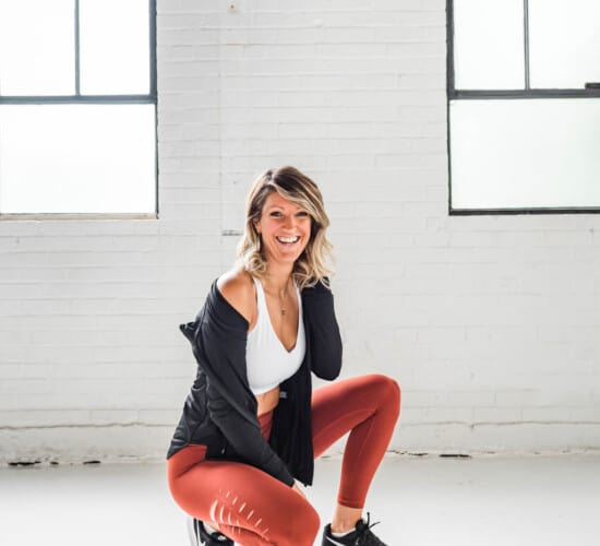 girl in workout clothes squatting and smiling