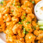 A Plate of Buffalo Cauliflower Bites Topped with Green Onions