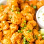 A Plate of Buffalo Cauliflower Wings Garnished with Chopped Green Onions