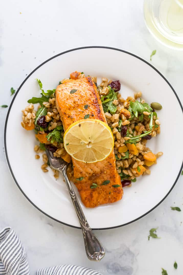 A Salmon Filet on a Plate with a Fork and a Slice of Lemon on Top