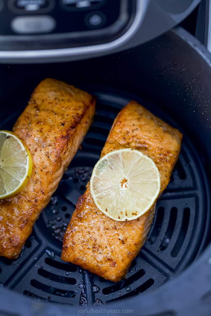 Two Salmon Filets in an Air Fryer with Lemon Slices on Top
