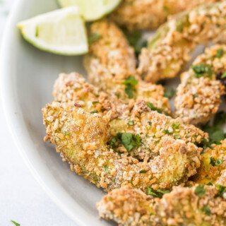 crispy avocado fries on a plate with lime wedges