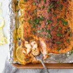 fork scooping baked salmon off of a baking sheet