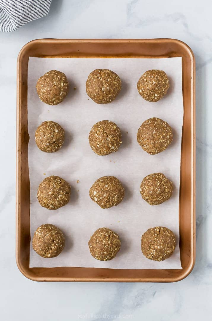 rolled energy bites on a baking sheet
