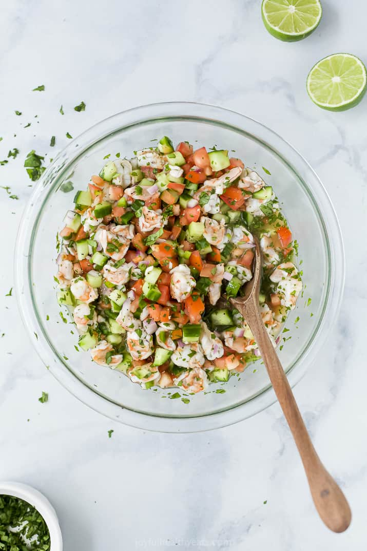 A Glass Bowl Filled with Seafood Ceviche and a Wooden Spoon