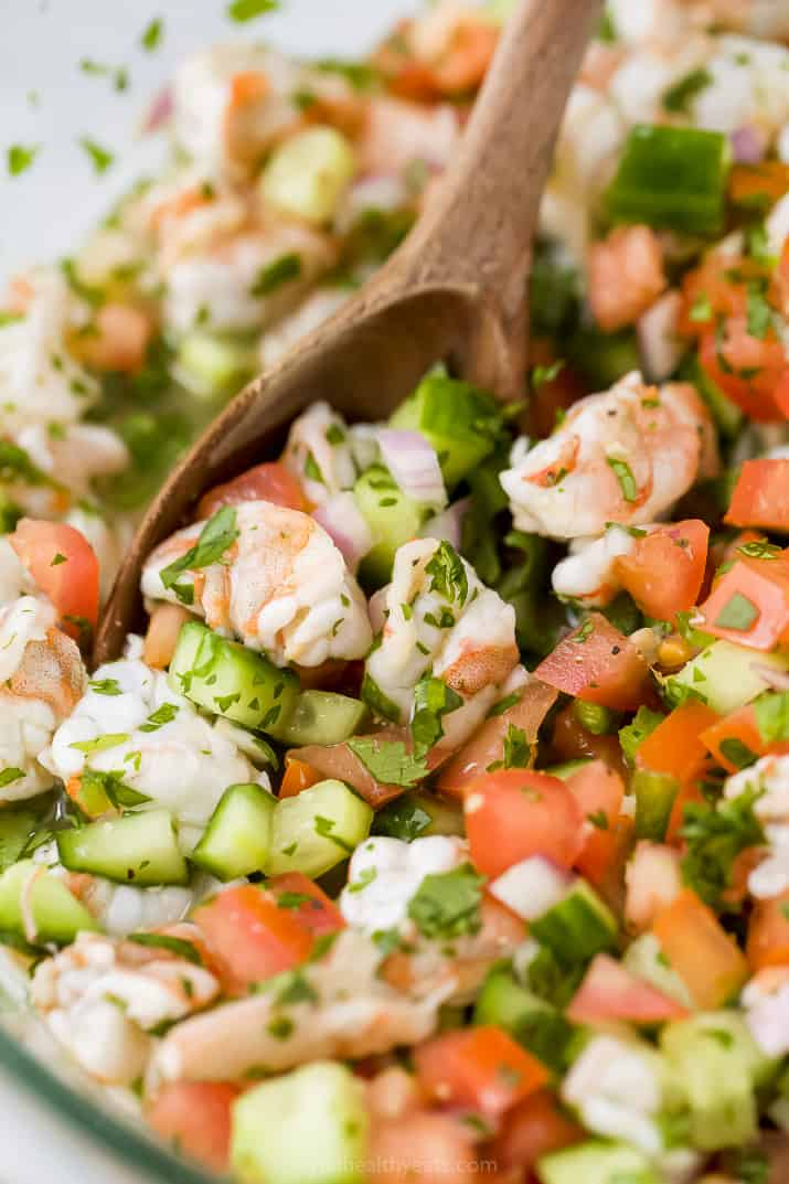 A Wooden Spoon Mixing Around Shrimp Ceviche in a Bowl