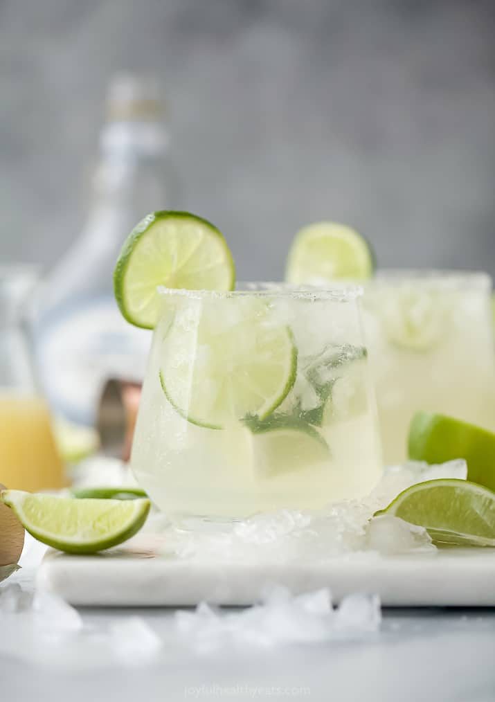 Two Glasses Filled with Homemade Margaritas and Pieces of Fresh Lime