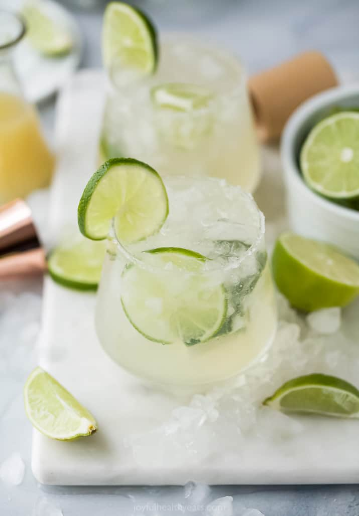 Two Margaritas on a Cutting Board with Lime Wedges and Crushed Ice