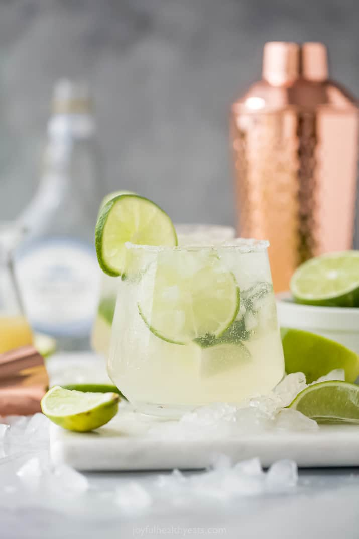 A Skinny Margarita in a Glass with a Cocktail Shaker in the Background