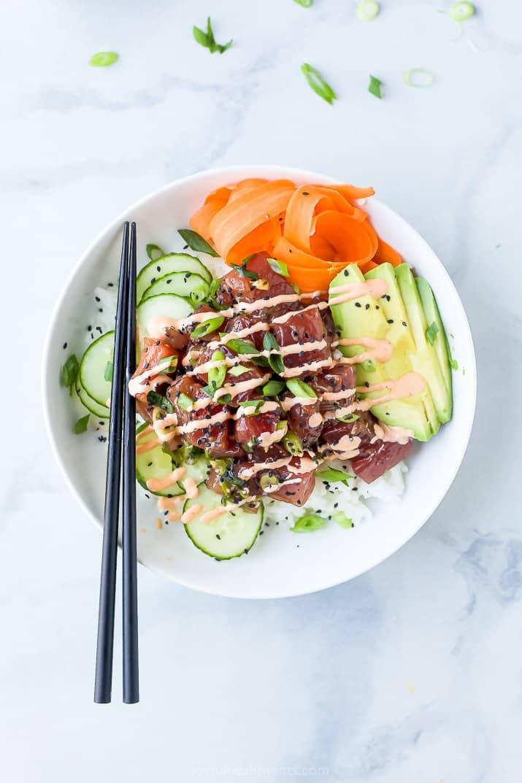 A White Bowl Containing Seasoned Tuna, Veggies, Rice and Sriracha Mayo
