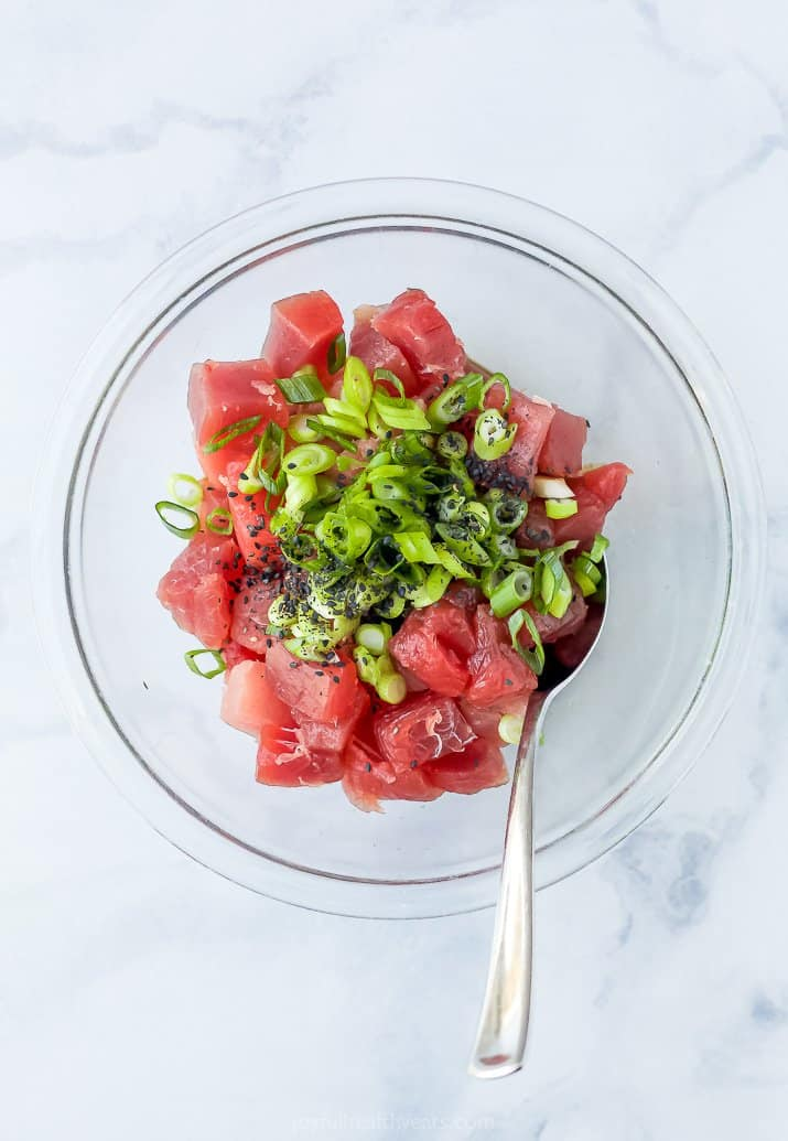 Pieces of Tuna in a Bowl with the Marinade Ingredients and a Spoon