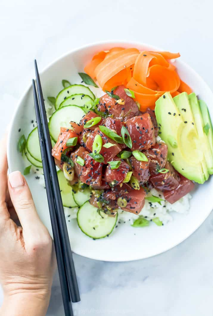 A Hawaiian Poke Bowl on a Countertop with a Hand on the Edge of the Bowl