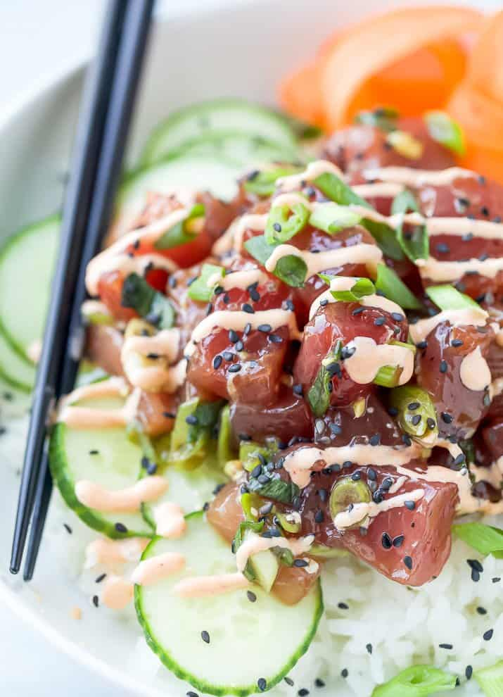 A Close-Up Image of a Tuna Poke Bowl Drizzled with Spicy Mayonnaise