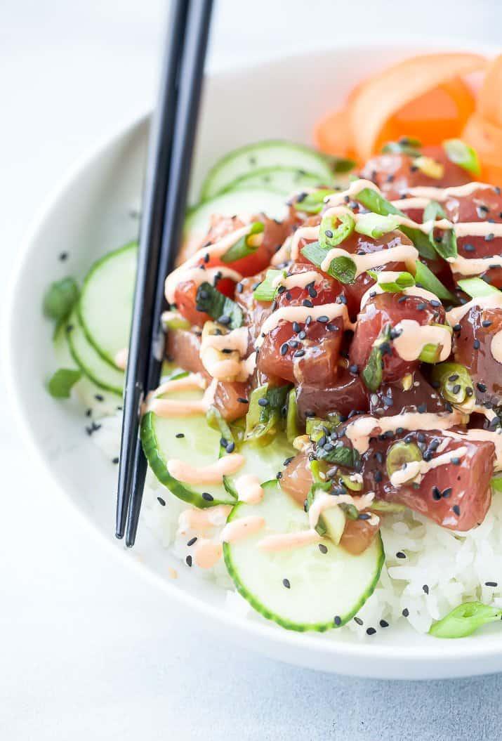 Rice, Bluefin Tuna, Sliced Cucumbers and More Veggies in a White Bowl