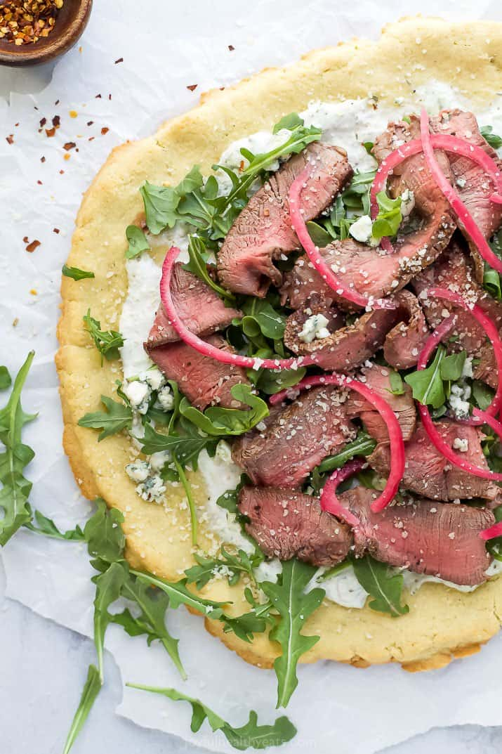 flatbread pizza topped with steak and arugula