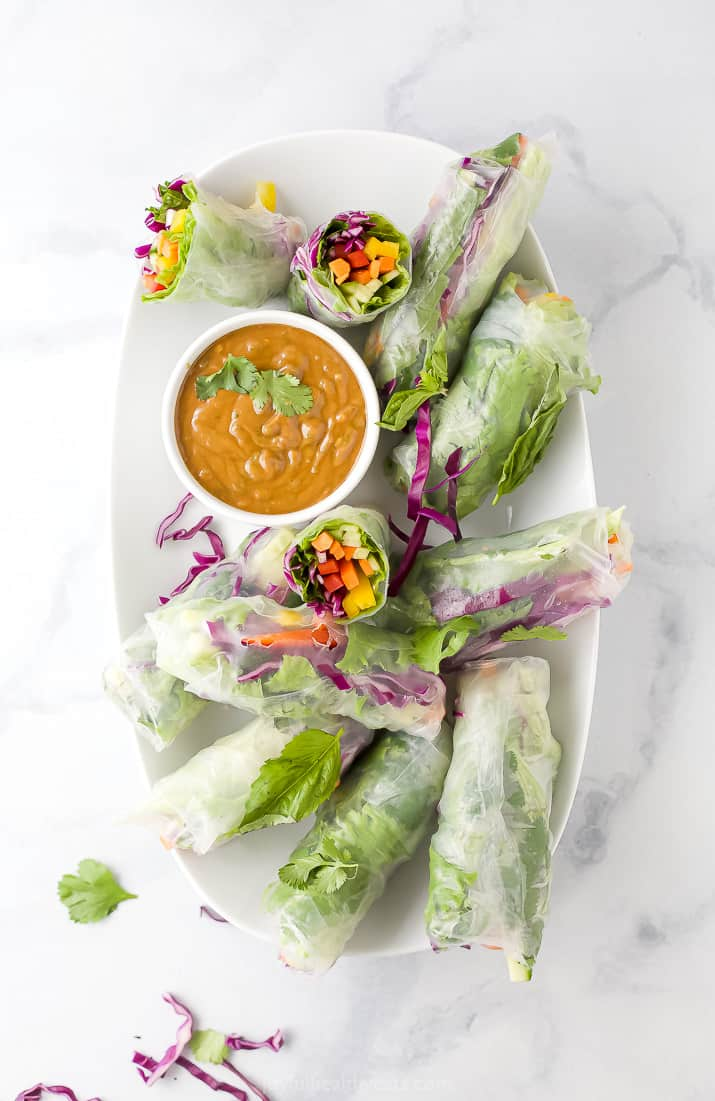 A Serving Dish Filled with Summer Rolls and a Small Bowl of Spicy Peanut Sauce