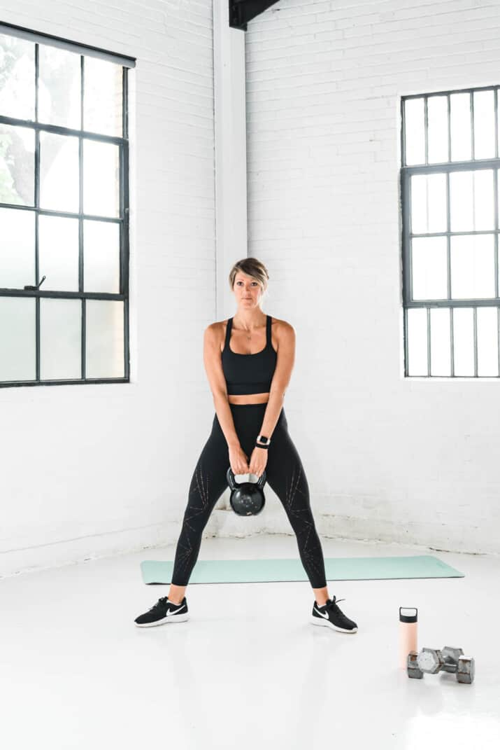girl holding a kettle bell doing sumo squats