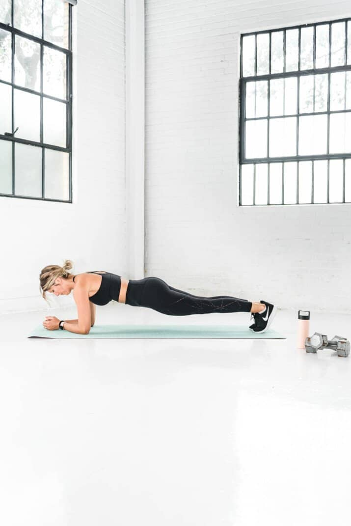girl in workout gear holding a plank position