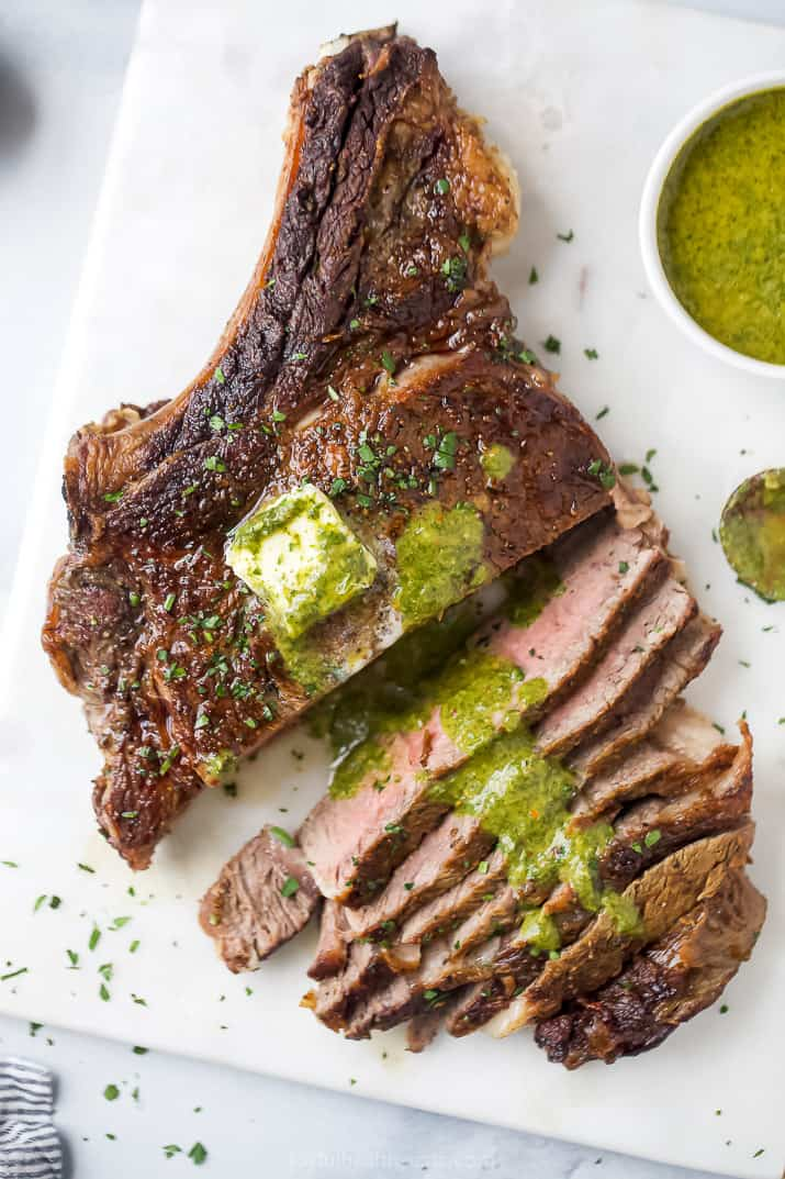 chimichurri sauce on top of a seared bone-in ribeye steak