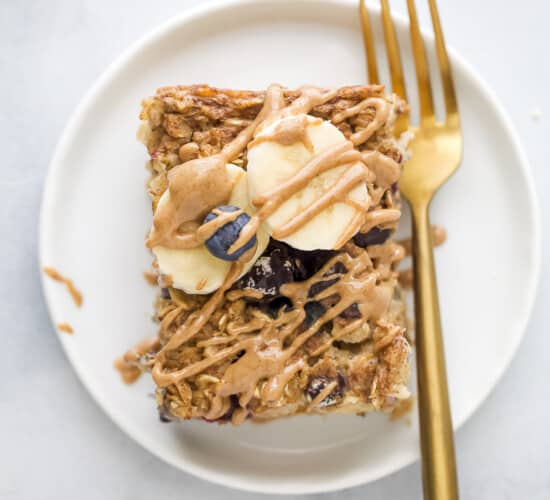 A slice of baked oatmeal on a white plate with a gold fork, topped with fresh blueberries, banana slices and almond butter