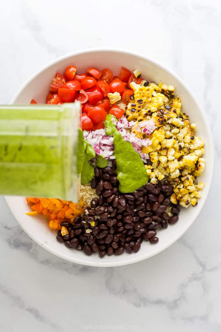 A big white bowl with tomato, charred corn, black beans, pepper, quinoa and onion, being topped with cilantro dressing to make a Mexican Quinoa Salad.
