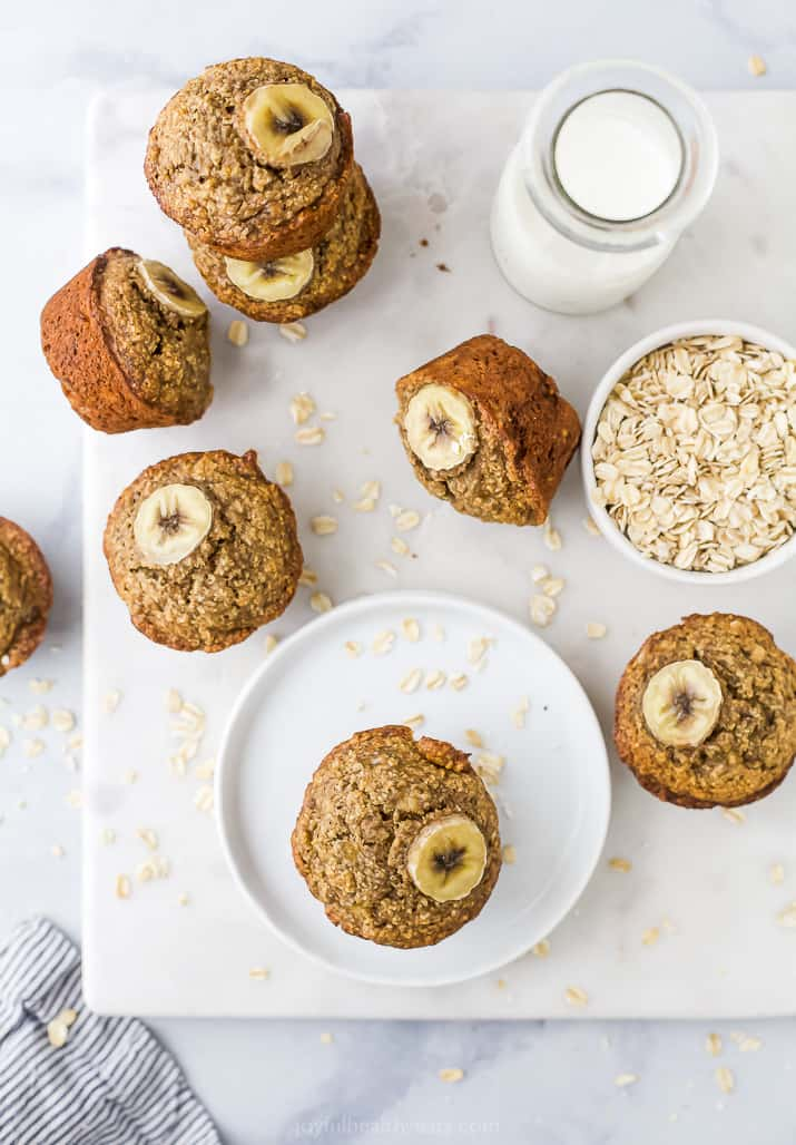 Aerial view of a banana muffin on a plate with more muffins, milk, and a bowl of oats next to it