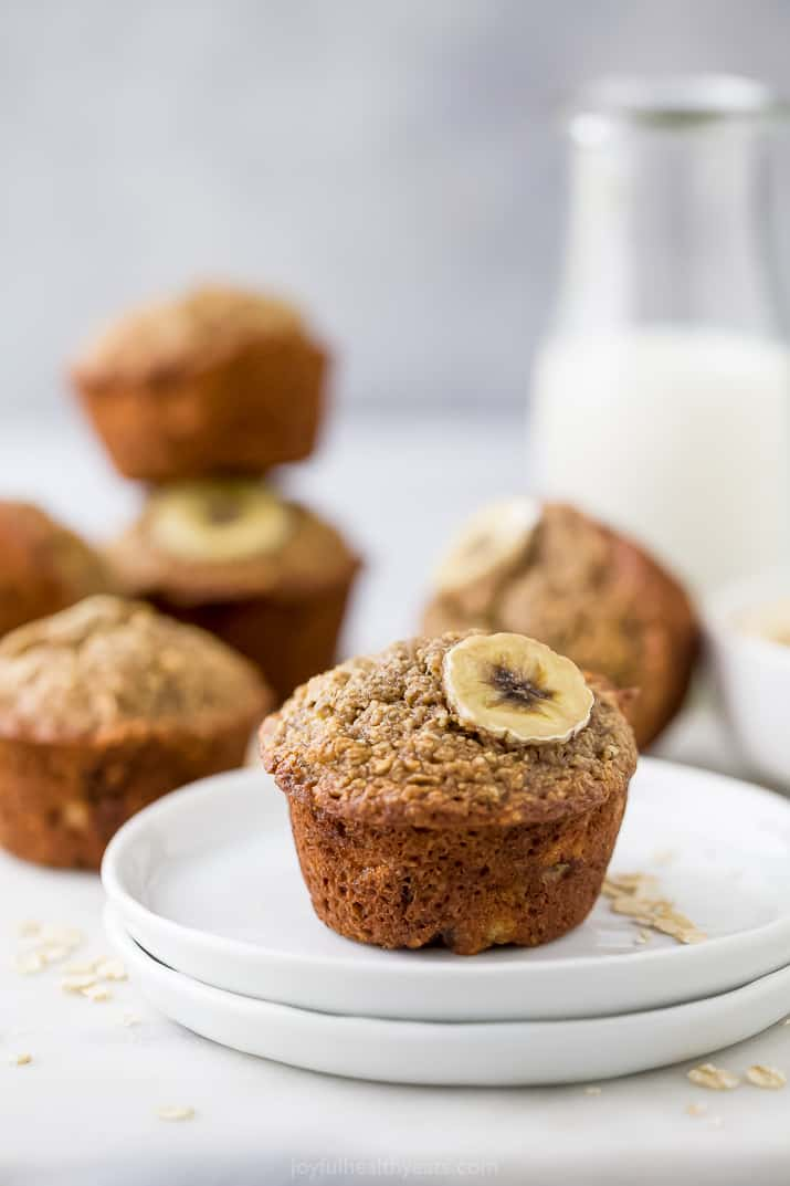 A banana muffin on a white, with more muffins and milk in the background