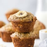 Banana oat muffins stacked on top of each other, with milk in the background