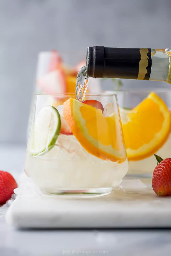 White wine being poured into a glass with ices, orange, lime and strawberry slices