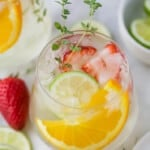 A glass of wine spritzer with strawberries, orange slices, and lime slices