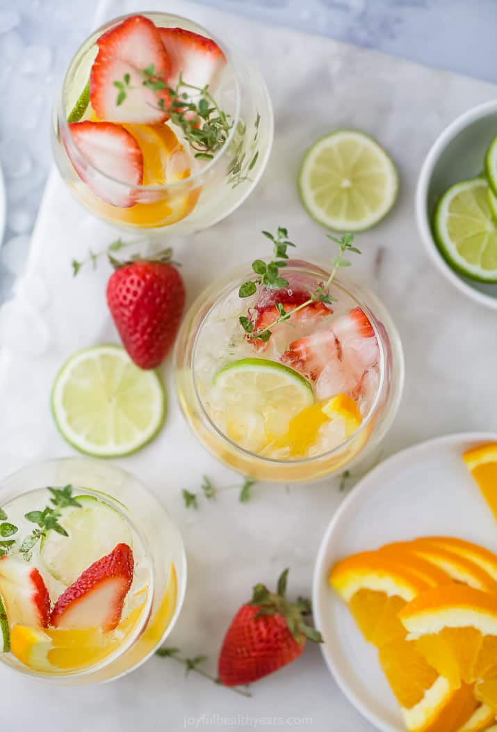 An aerial view of three glasses of white wine spritzer, with orange and lemon slices and strawberry