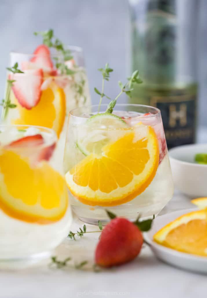 Glasses of white wine spritzer with orange slices
