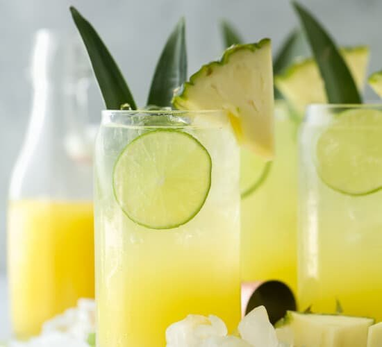 glass filled with pina colada spritzer with pineapple garnish