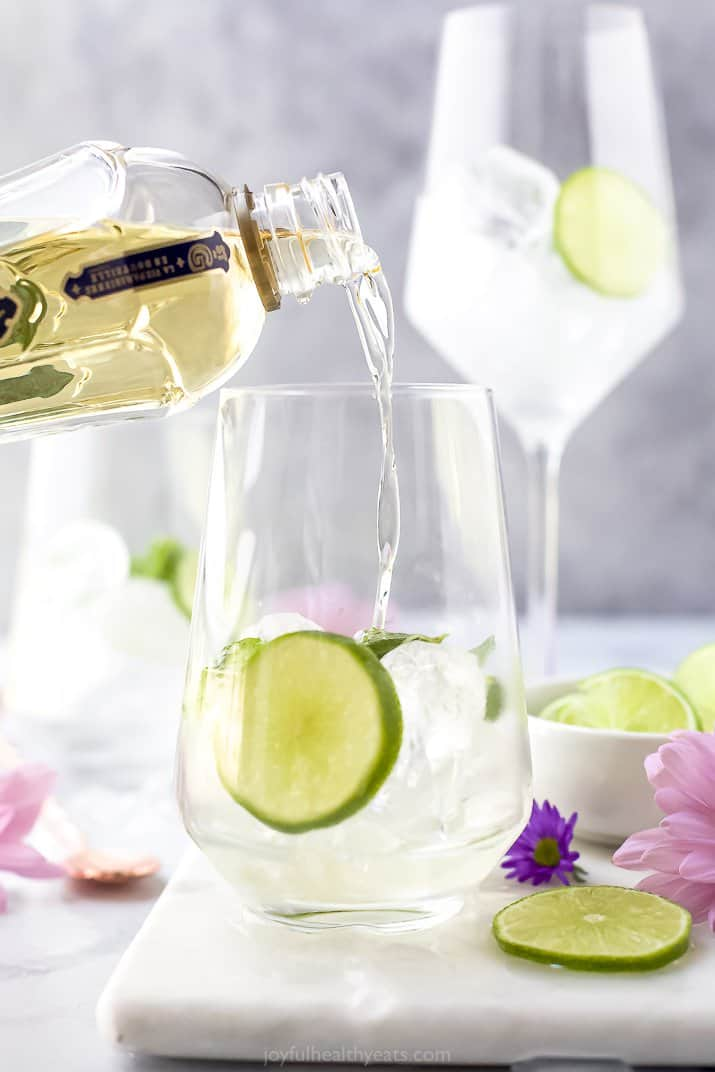 St. Germain being poured into a wine glass with ice and lime slices