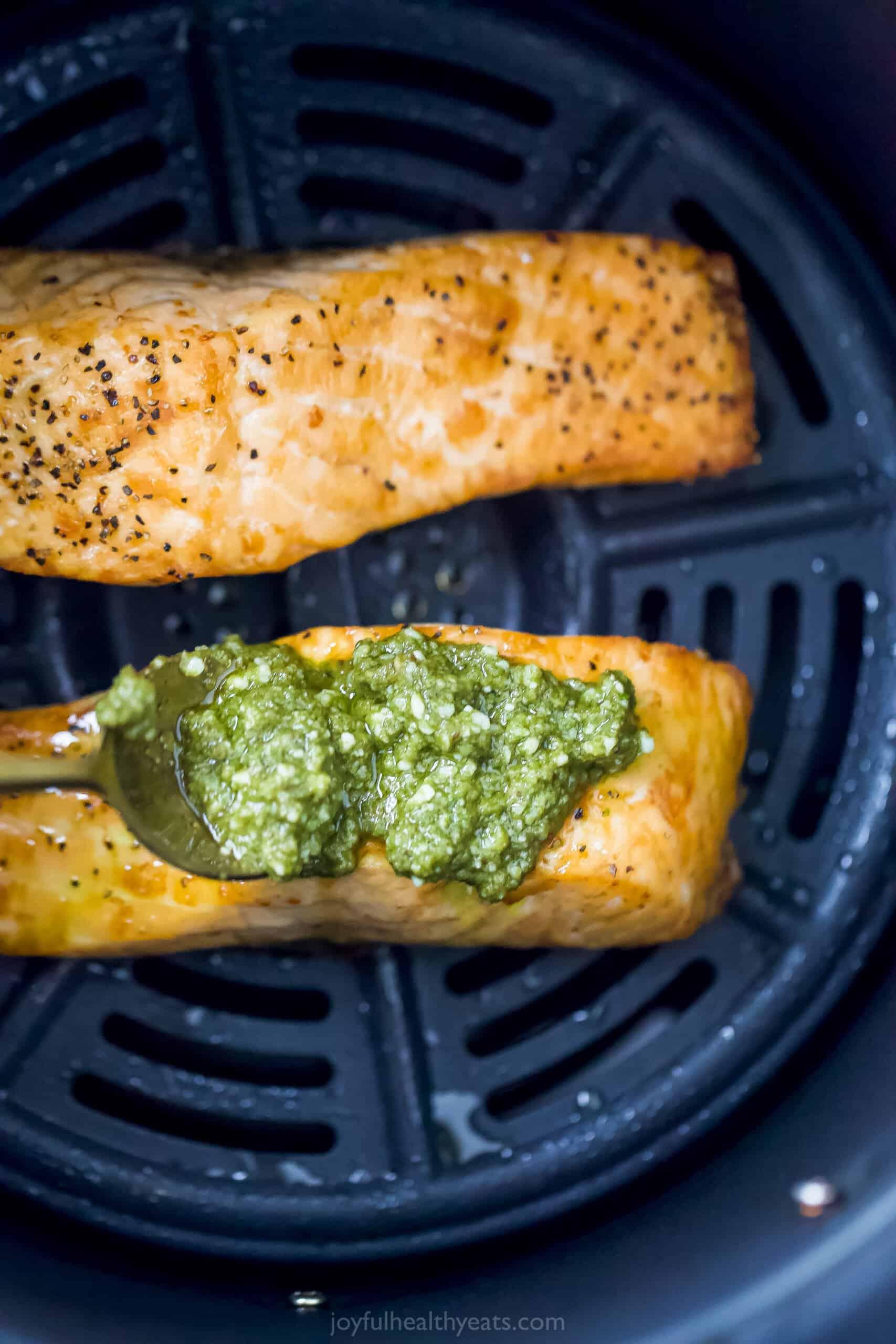 pesto being spread on salmon in air fryer