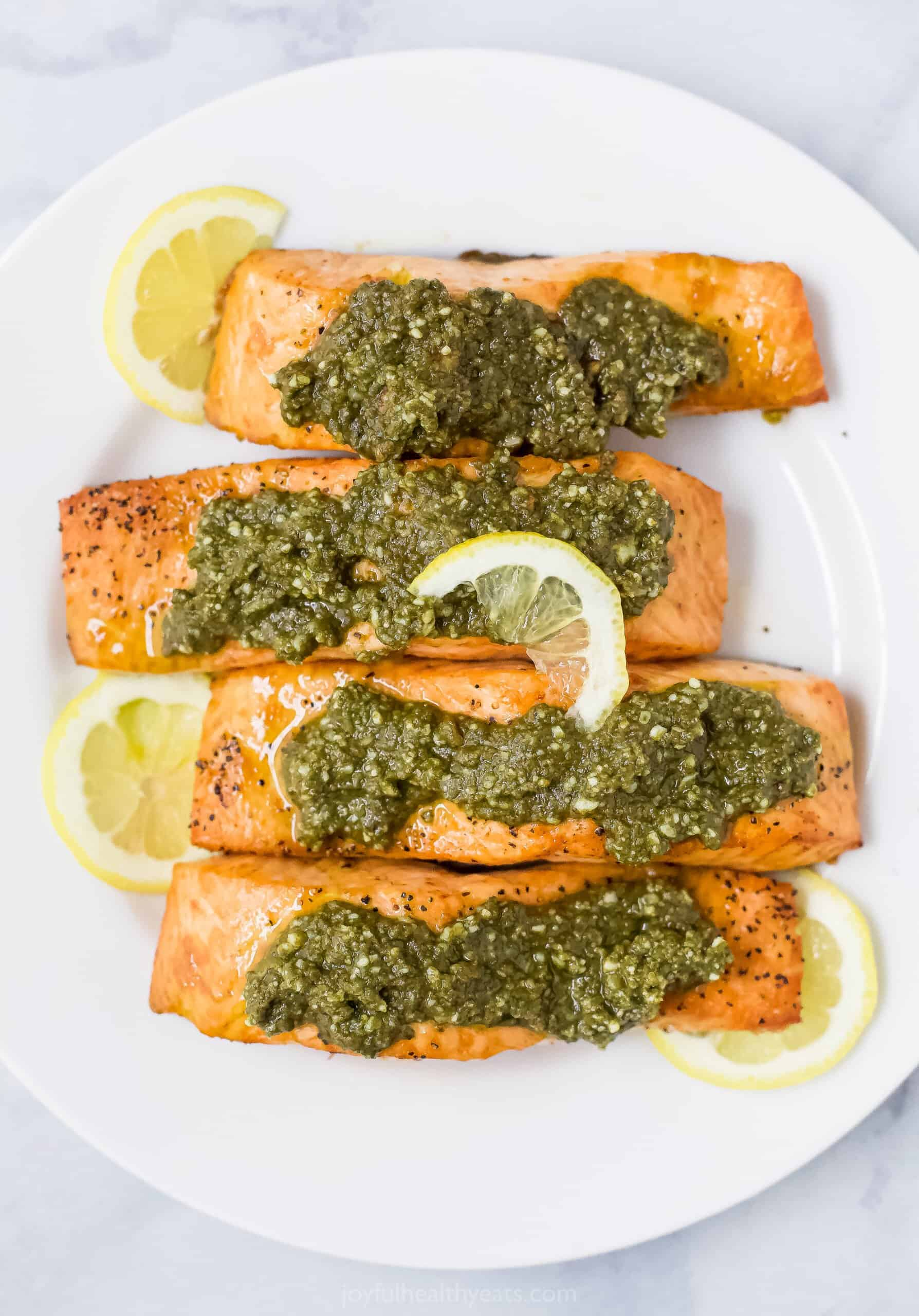 salmon filets on a plate topped with basil pesto