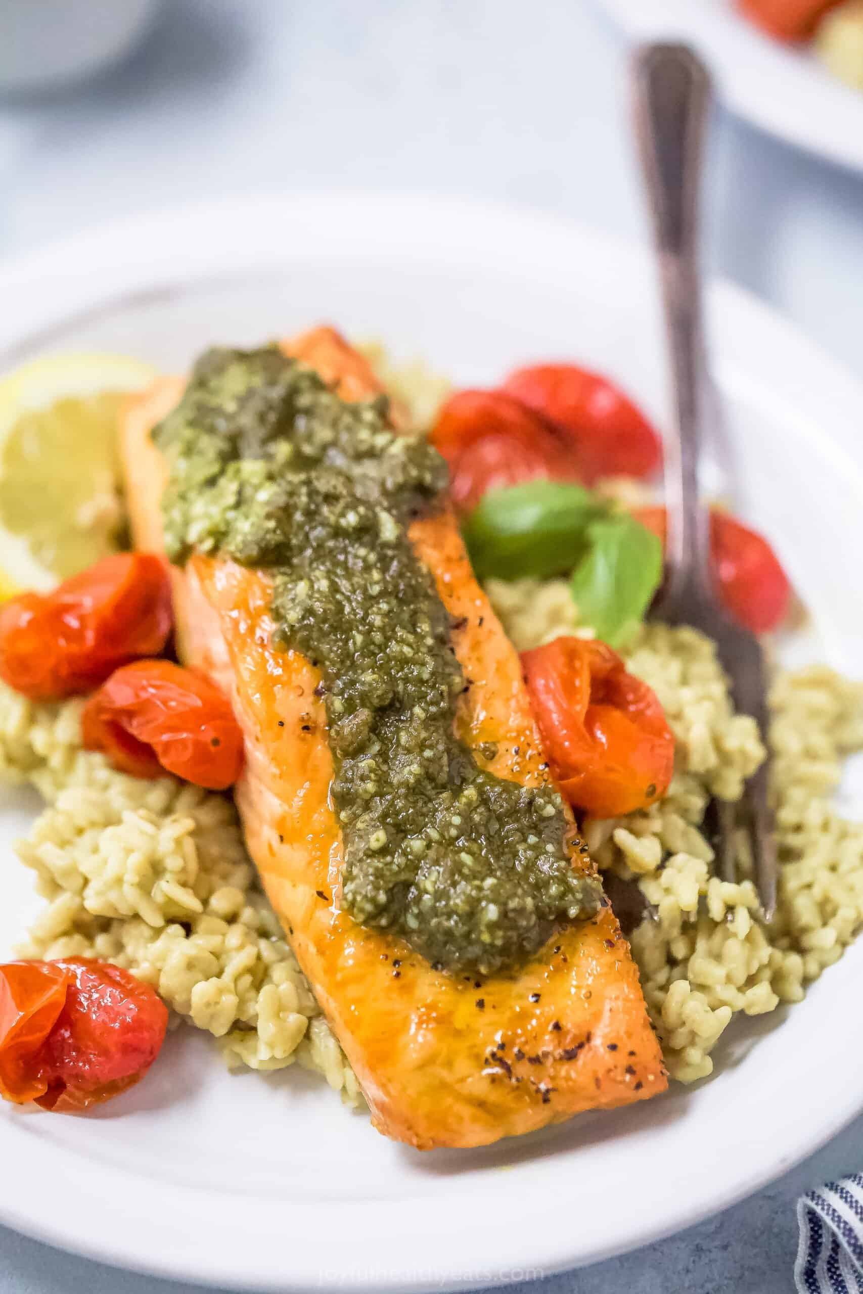 air fryer pesto salmon on top of rice with tomatoes