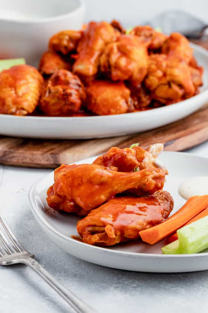 A Serving of Baked Buffalo Chicken Wings on a White Plate with a Platter Full of Wings in the Background
