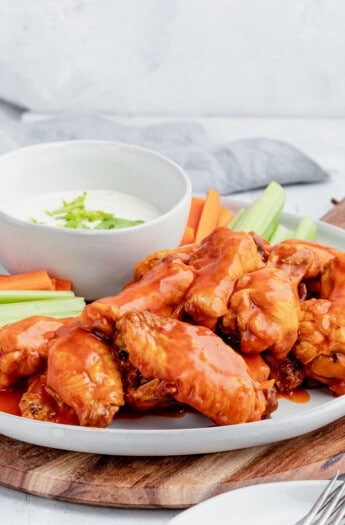 A Serving Platter Piled with Homemade Chicken Wings and Raw Vegetables