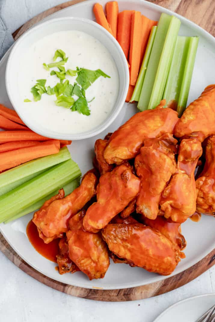 Baked Buffalo Chicken Wings Piled Onto a Plate with Raw Vegetables and Ranch Dressing