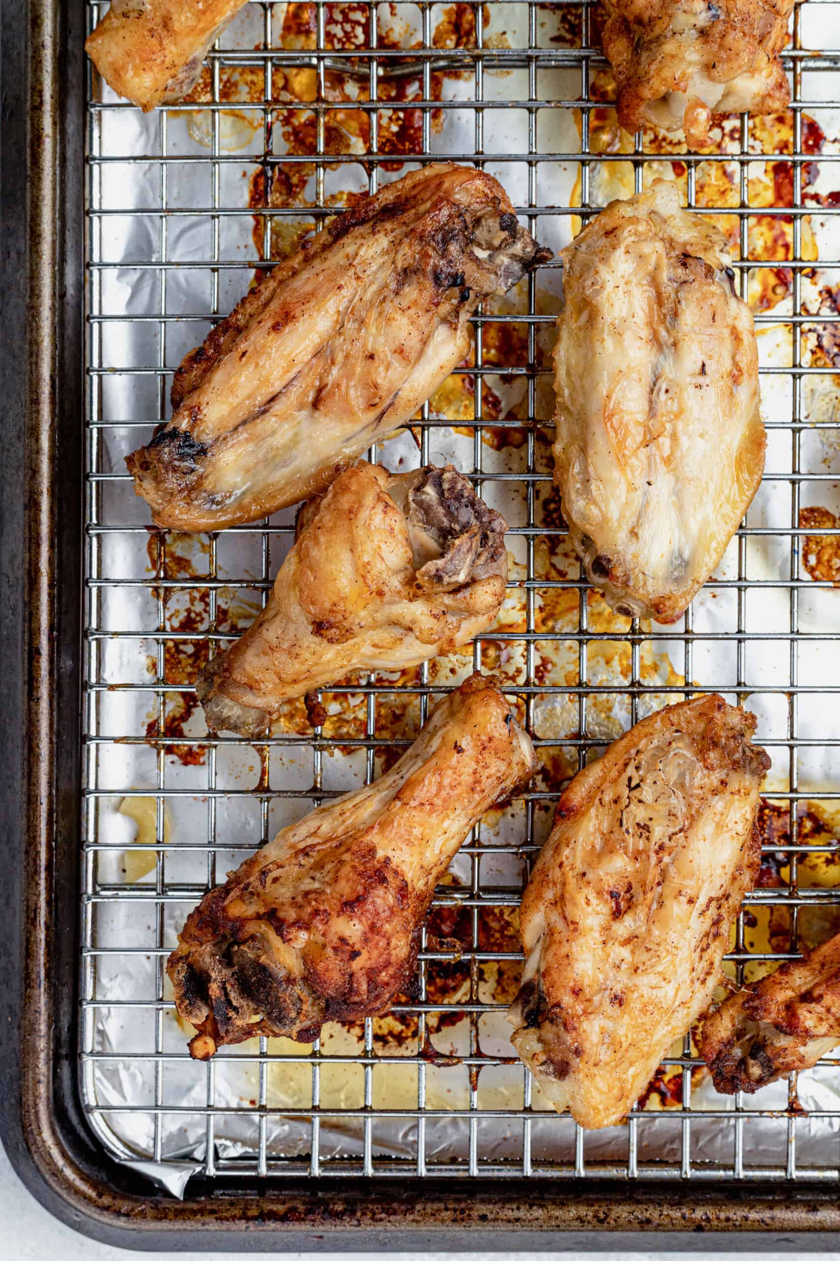Baked Chicken Wings on a Wire Rack Over a Baking Sheet Lined with Aluminum Foil