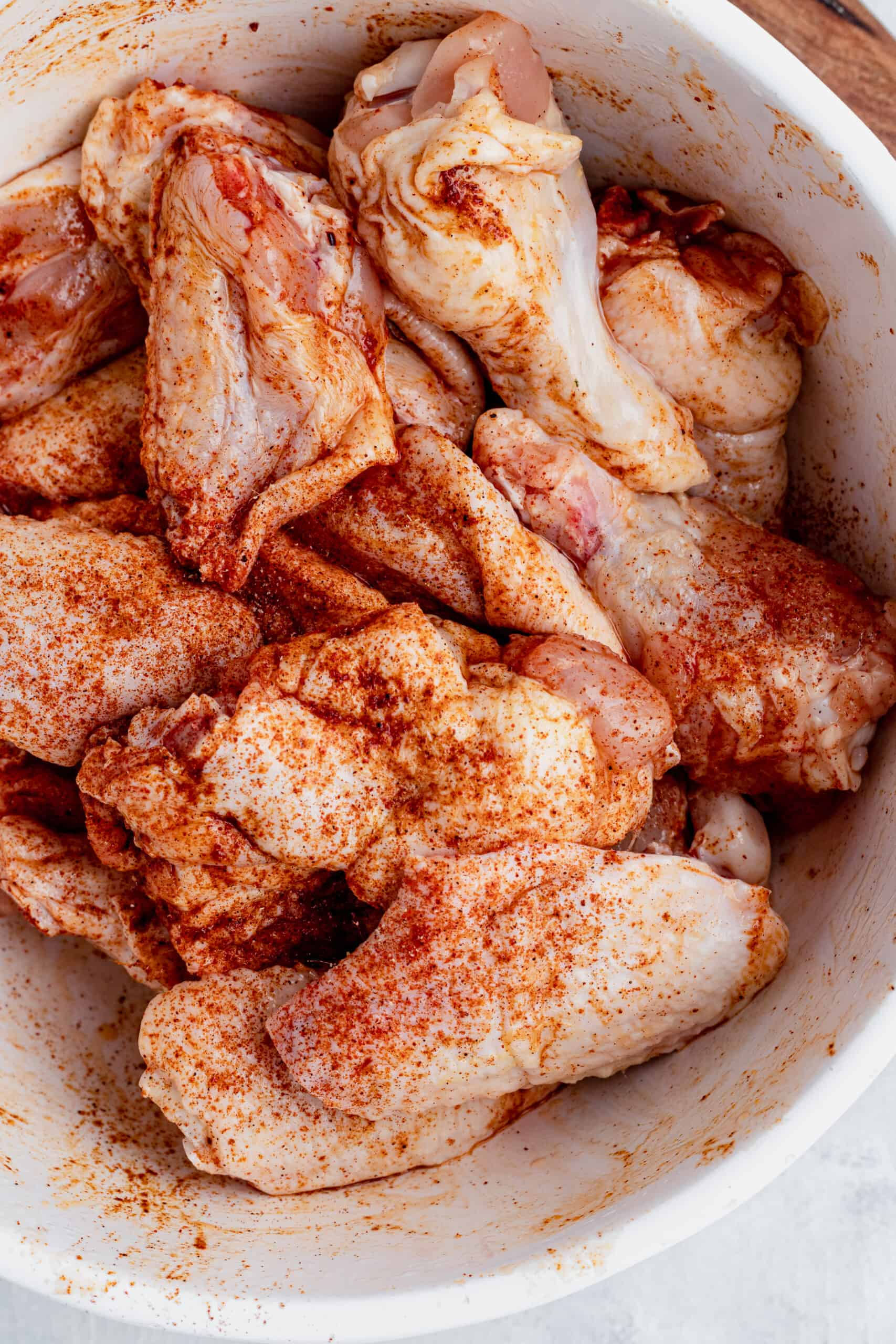 A Bowl of Raw Chicken Wings Coated in Spices