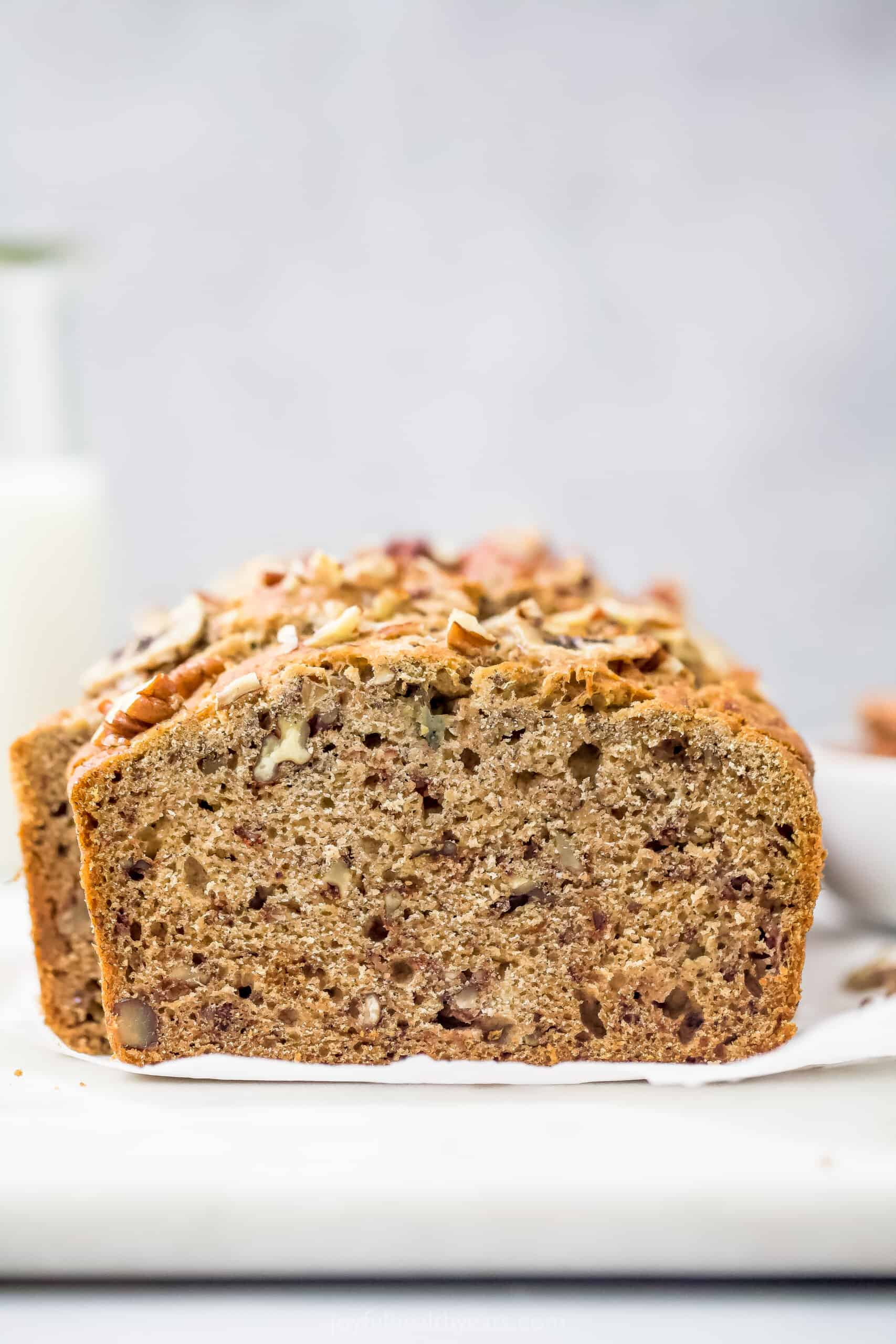 A Loaf of Banana Nut Bread on a White Surface with a Glass of Milk in the Background