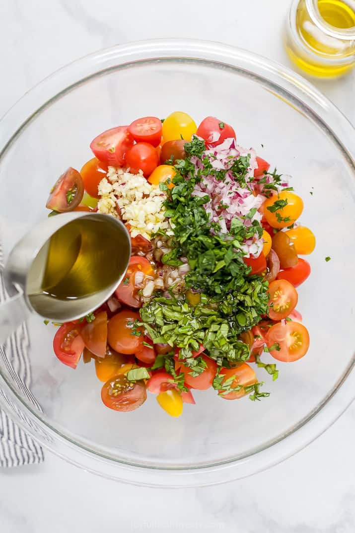 pouring marinade over tomato salad