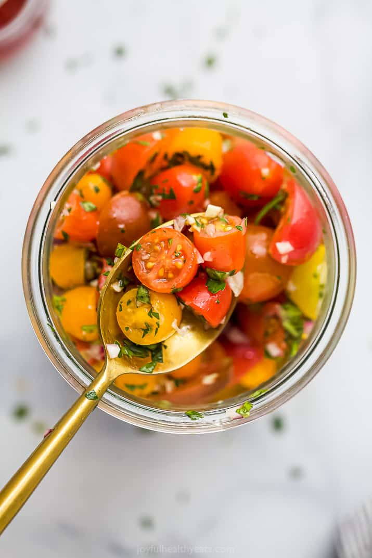 spoon scooping tomato salad