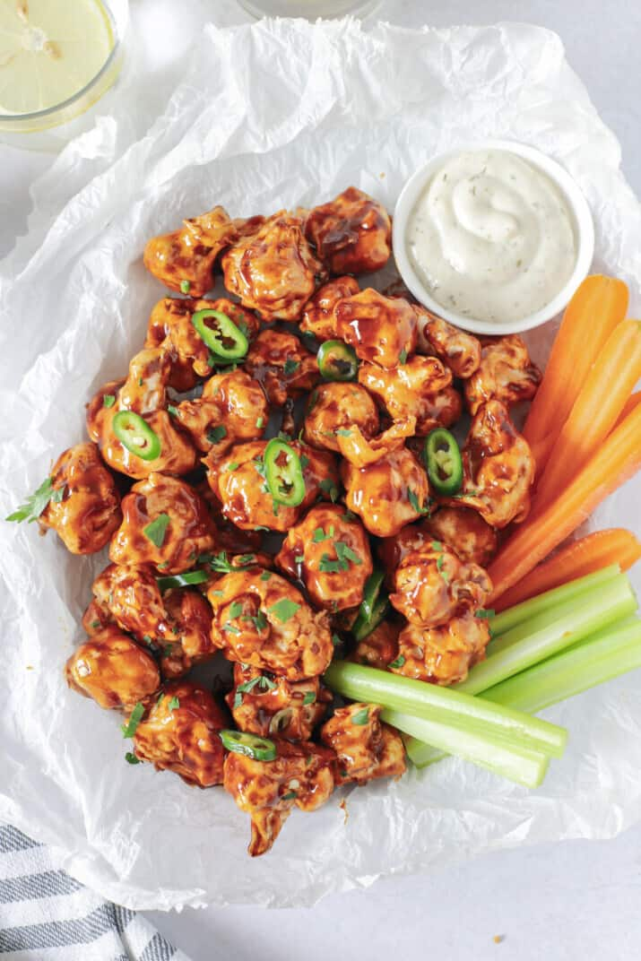 air fryer cauliflower wings tossed with honey bbq sauce in a basket