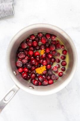 frozen cranberries with orange juice in a pot
